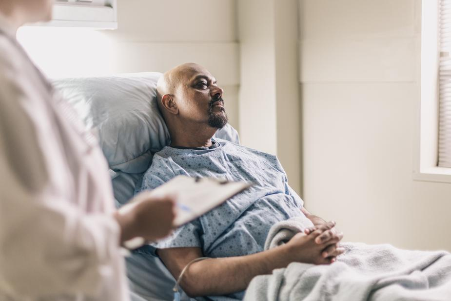 a-man-lies-in-a-hospital-bed-as-a-doctor-reads-his-chart