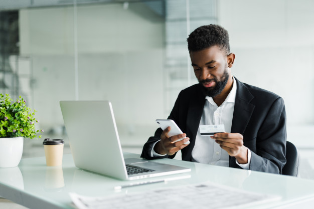 african-american-man-paying-with-credit-card-online-while-making-orders-via-mobile-internet-making-transaction-using-mobile-bank-application_231208-739