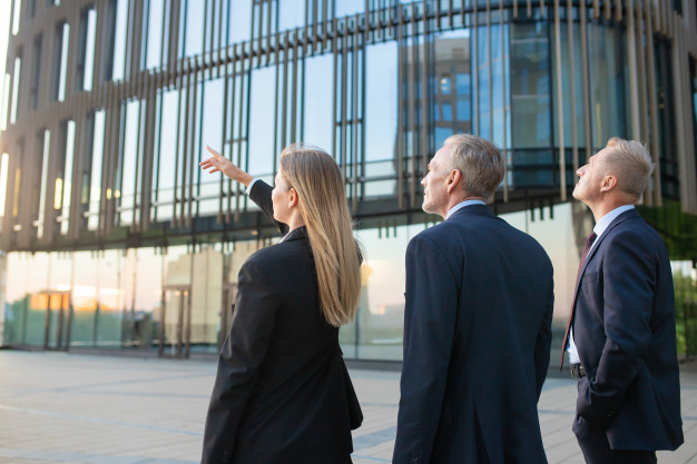 agent-customers-meeting-outdoors-discussing-real-property-pointing-office-building-back-view-commercial-real-estate-concept_74855-6738