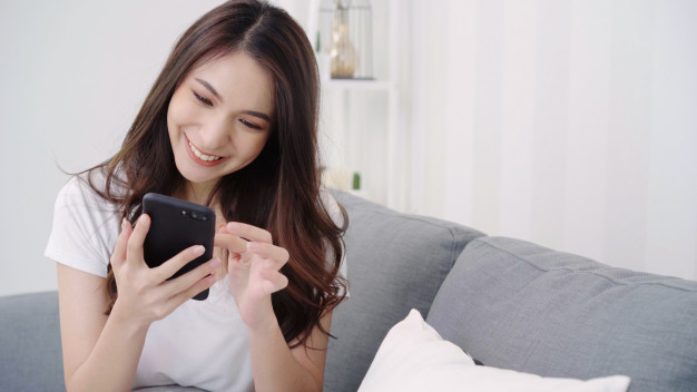 asian-woman-playing-smartphone-while-lying-home-sofa-her-living-room_7861-1660