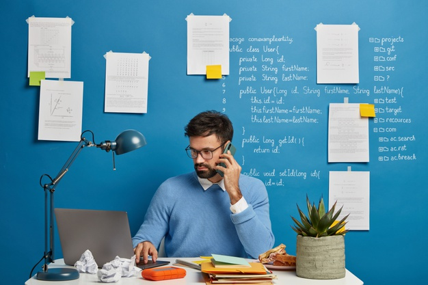 bearded-man-talks-about-initializing-database-information-focused-laptop-computer-wears-spectacles-vision-protection-checks-application-sits-desktop_273609-34353