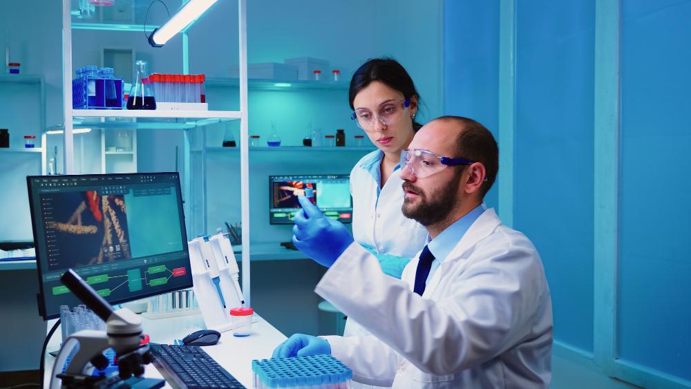 chemist-doctor-explaining-nurse-vaccine-development-modern-equipped-laboratory-holding-test-tube-with-blood-sample