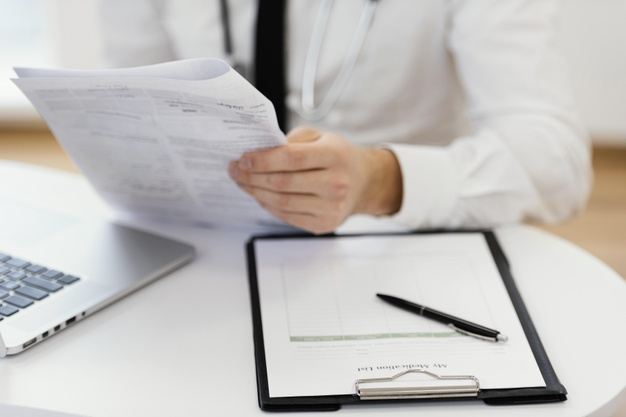 close-up-doctor-holding-medical-records_23-2148868184