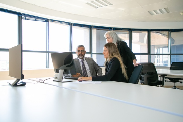 company-managers-discussing-solution-businesspeople-gathering-meeting-room-watching-content-computer-monitor-together-business-communication-teamwork-concept_74855-11621