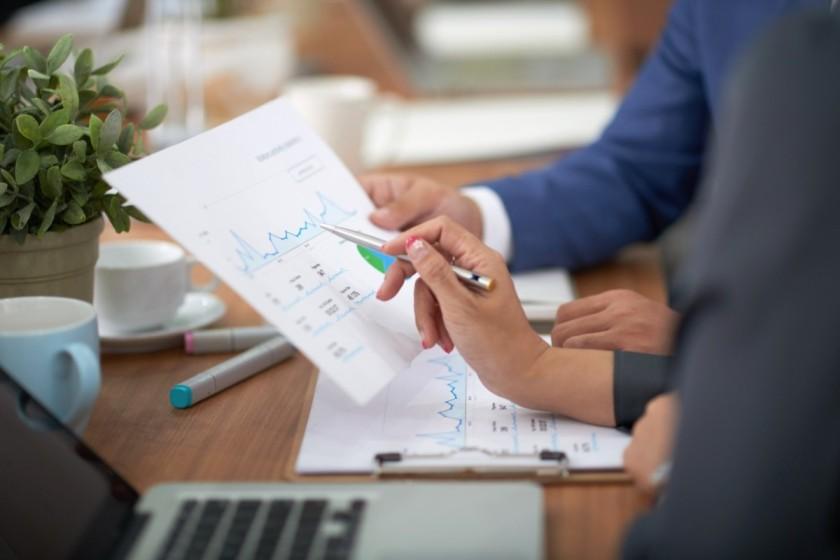 hands-man-woman-business-attire-sitting-desk-office-discussing-graph (1) (1) (1) (1) (1)