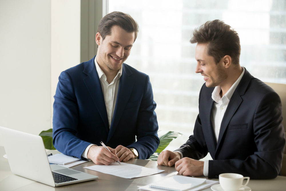 handsome-businessman-signing-contract-with-partner
