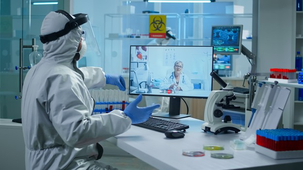 lab-technician-ppe-suit-sitting-table-medical-research-laboratory-holding-test-tube-talking-video-call-with-senior-doctor-giving-online-advices-during-virtual-meeting_482257-531