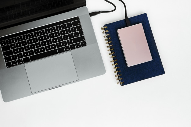 Pink external hard disk connecting to a laptop