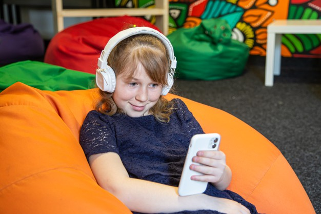 little-girl-uses-phone-listens-music-with-headphones-while-sitting-bag-chair_169016-11839