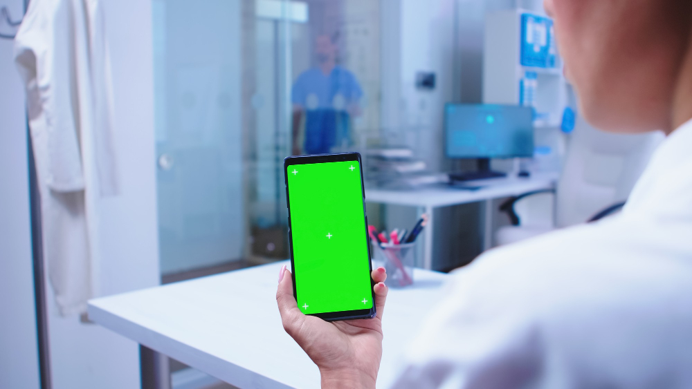 medical-physician-looking-phone-with-green-screen-hospital-cabinet-nurse-getting-out-elevator-healthcare-specialist-hospital-cabinet-using-smartphone-with-mockup