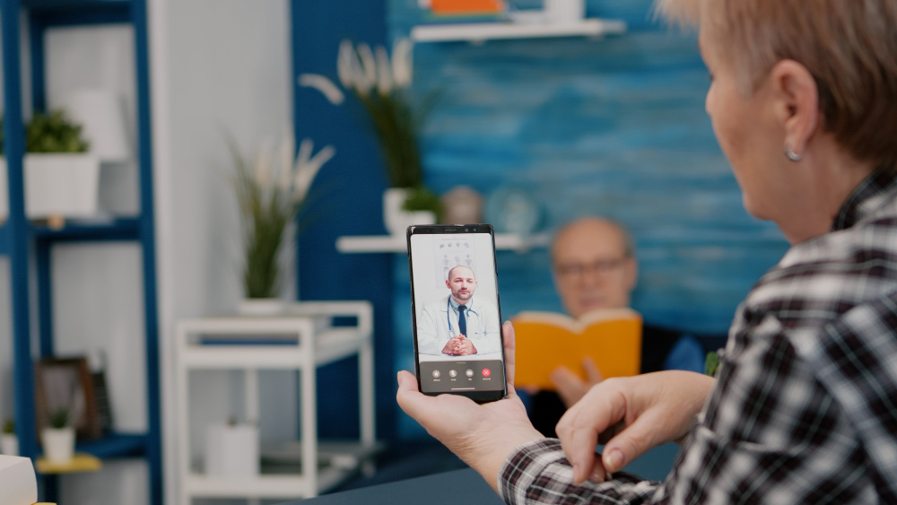 middle-aged-woman-talking-video-conference-calling-with-remote-doctor-using-smartphone