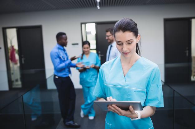 nurse-using-digital-tablet-hospital-corridor_107420-84829