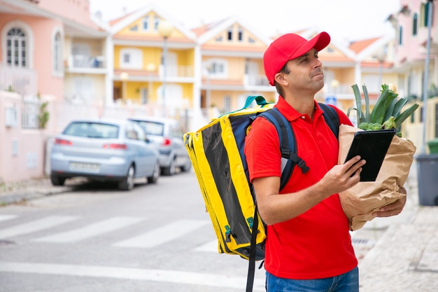 pensive-courier-with-isothermal-food-backpack-using-tablet-checking-address-medium-shot-copy-space-communication-delivery-service-concept_74855-11879