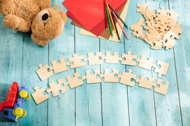 pieces-puzzles-surface-wooden-table-with-toys-colors_155003-35836