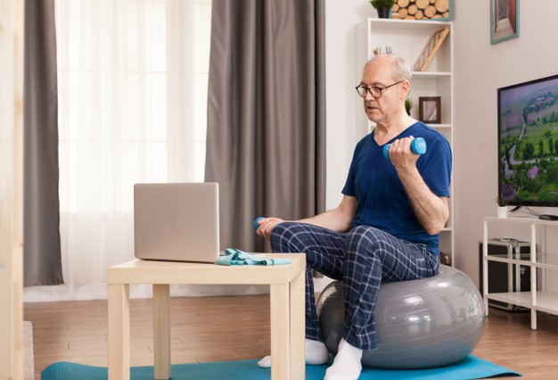senior-man-training-with-online-coach-sitting-swiss-ball-middle-room_482257-119