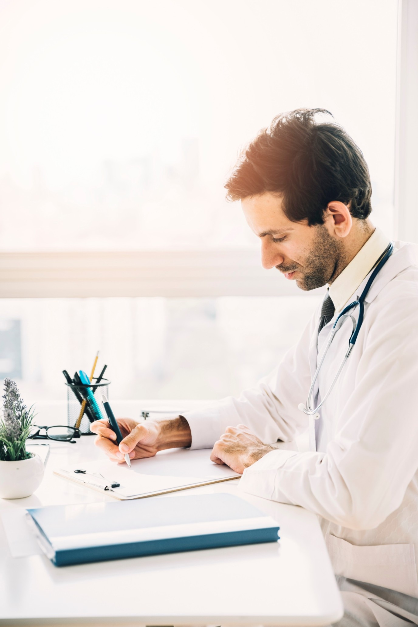 side-view-young-male-doctor-writing-clipboard-clinic (1) (1) (1)