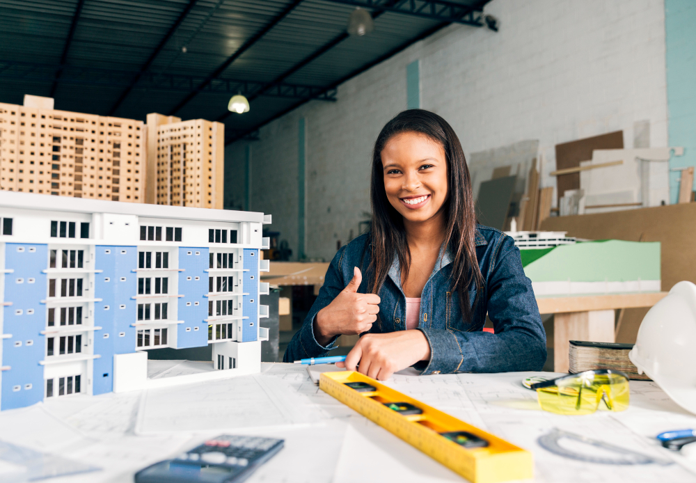 smiling-african-american-woman-showing-thumb-up-near-model-building