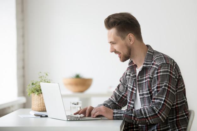 smiling-man-freelancer-working-laptop-communicating-online-using-software_1163-4611