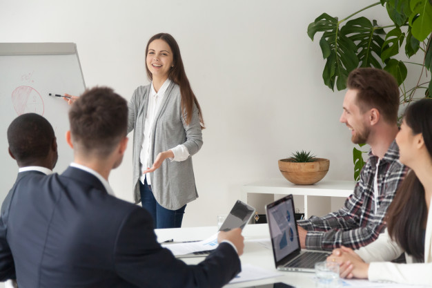smiling-young-employee-giving-presentation-working-with-flipchart-meeting-room_1163-4622