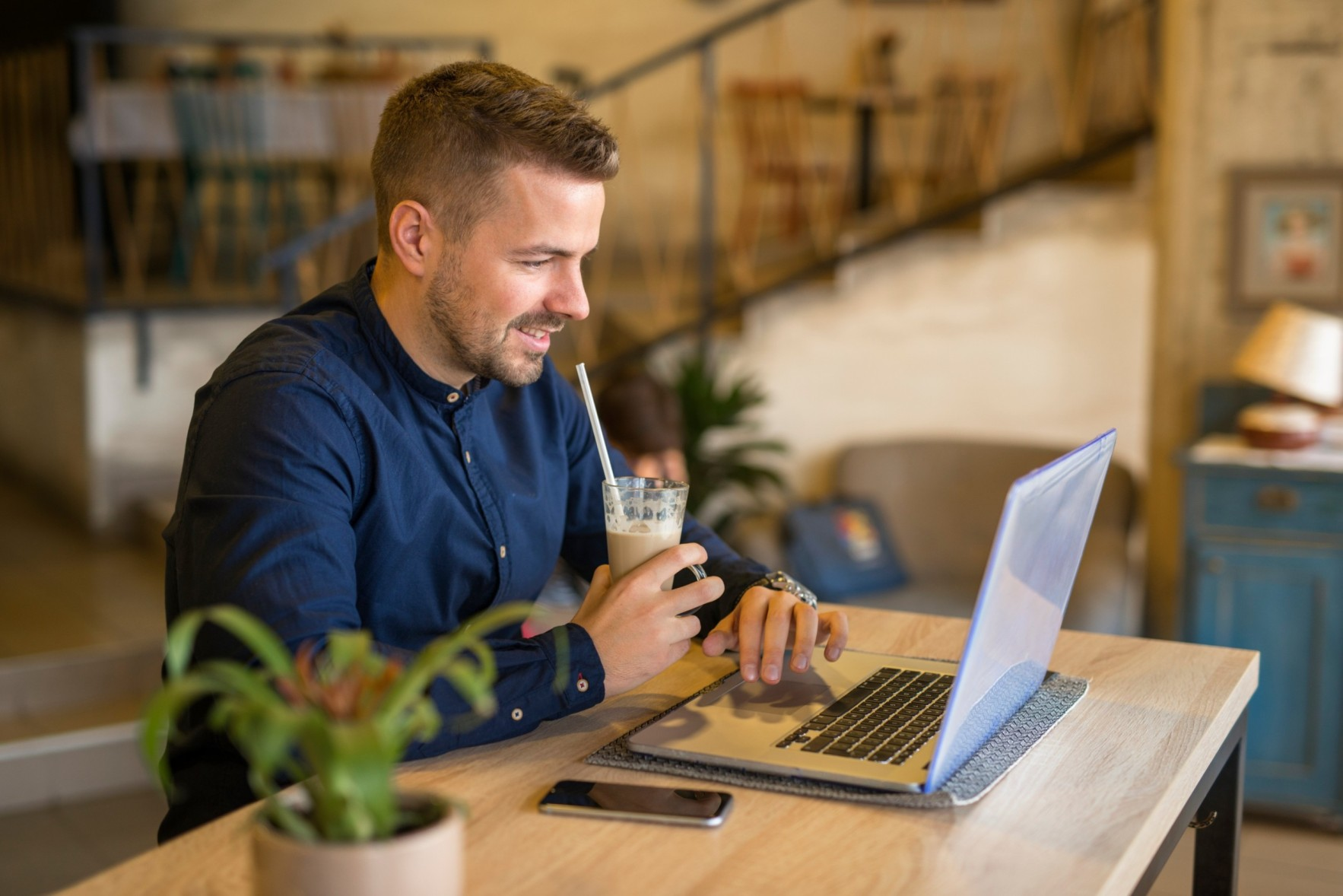 smiling-young-man-working-computer-cozy-cafe-bar-restaurant (1) (1) (1) (1)