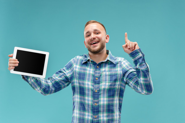 studio-picture-positive-man-isolated-blue-wall-standing-casual-clothes-holding-tablet-showing-it-blank-screen-with-happy-smile_155003-9340