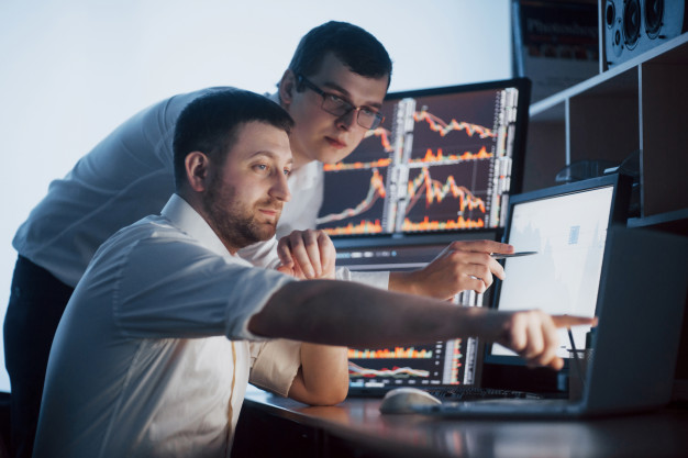 team-stockbrokers-are-having-conversation-dark-office-with-display-screens-analyzing-data-graphs-reports-investment-purposes-creative-teamwork-traders_146671-15017