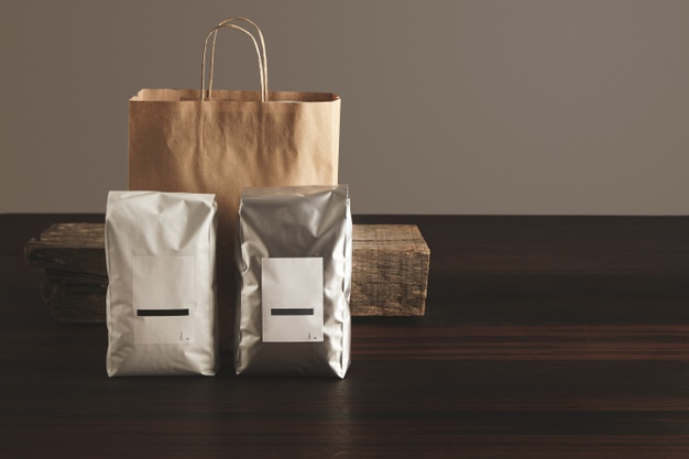 two-big-hermetic-packages-with-blank-labels-presented-front-craft-paper-bag-rustic-wooden-brick-red-table_346278-406
