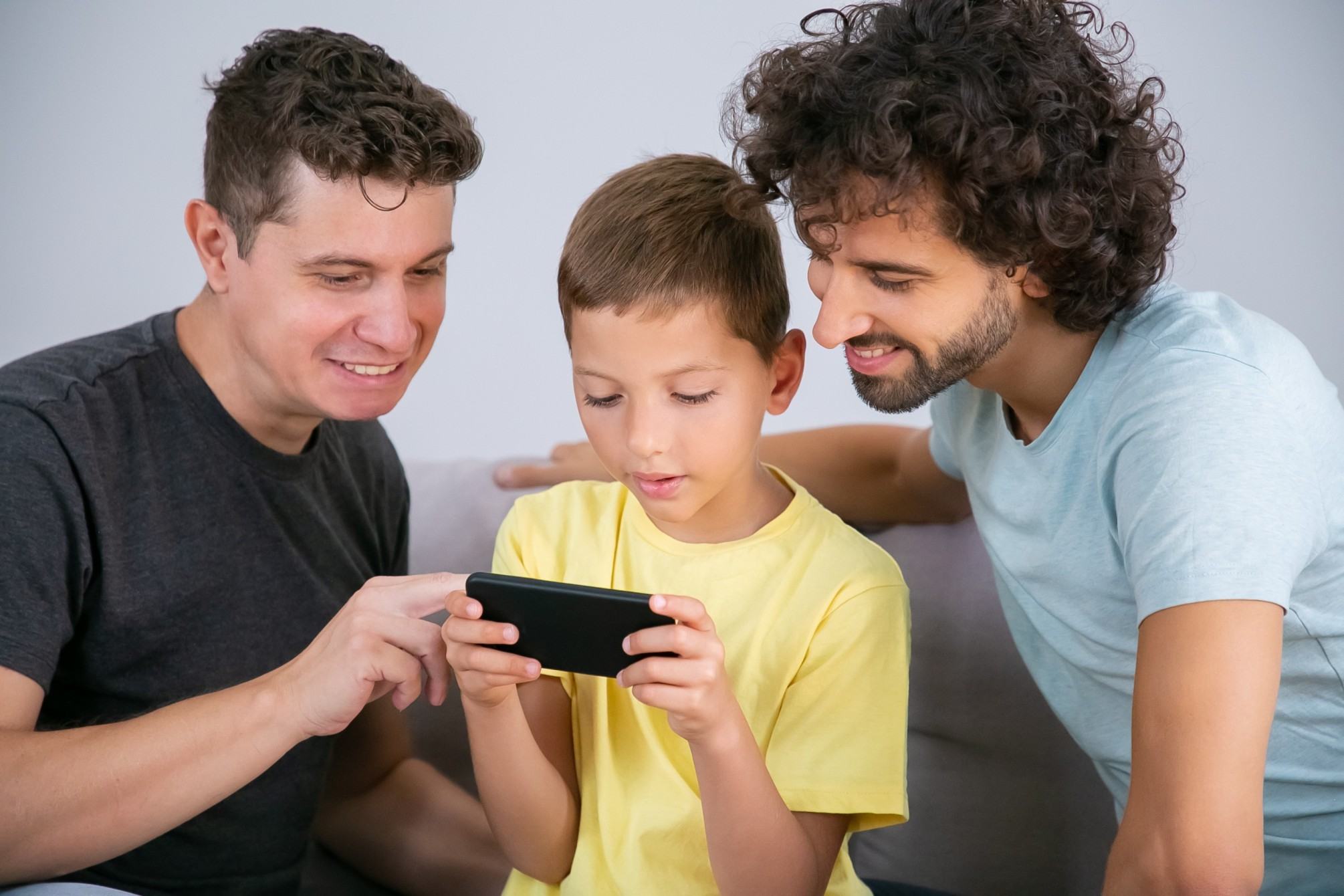 two-happy-dads-teaching-son-use-online-app-cell-boy-playing-game-mobile-phone-family-home-communication-concept (1) (1)
