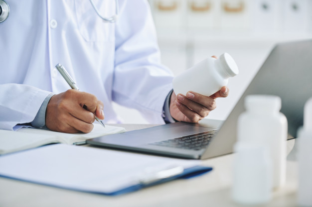 unrecognizable-female-doctor-with-laptop-holding-medication-writing-prescription_1098-17464
