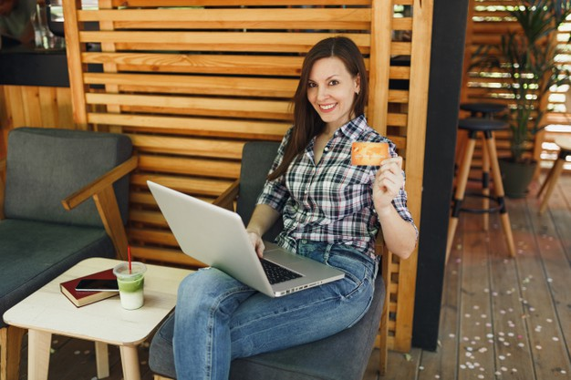 woman-outdoors-street-summer-coffee-shop-wooden-cafe-sitting-working-laptop-pc-computer-hold-bank-credit-card-relaxing-during-free-time_365776-3941