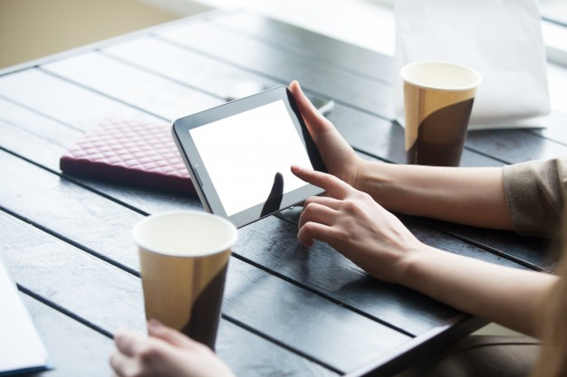 women-hands-holding-tablet-with-white-blank-screen-cafe-close-up_1163-1644