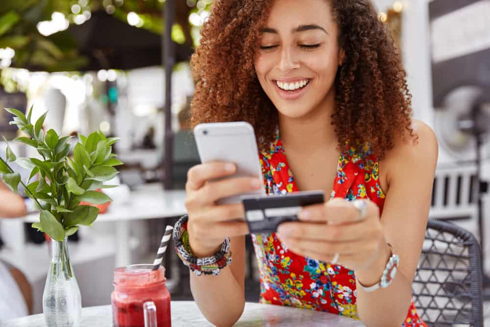 beautiful-dark-skinned-young-female-with-cheerful-expression-holds-smart-phone-credit-card-banks-online-makes-shopping-while-sits-against-cafe-interior