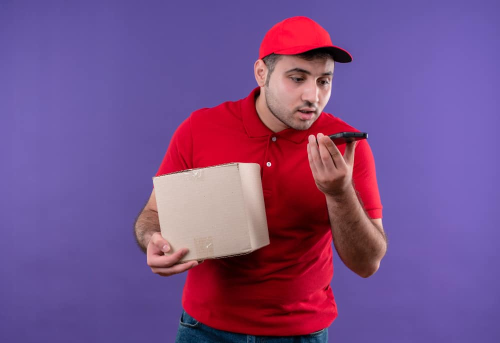 young-delivery-man-red-uniform-cap-holding-box-package-sending-voice-message-using-his-smartphone-standing-purple-wall